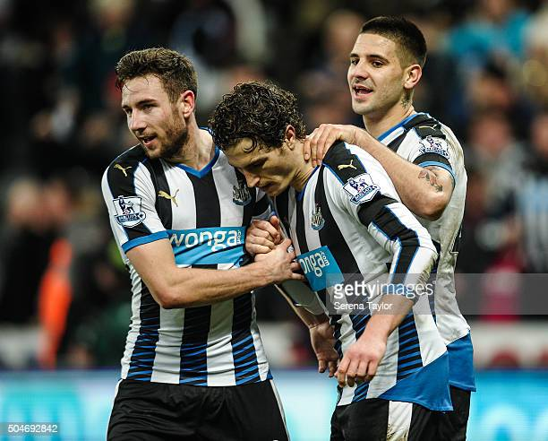 Paul Dummett of Newcastle celebrates with teammates Daryl Janmaat and Aleksandar Mitrovic after scoring Newcastle's third and equalising goal during...