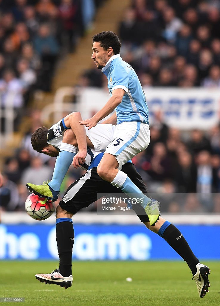 Paul Dummett of Newcastle United and Jesus Navas of Manchester City commpete for the ball during the Barclays Premier League match between Newcastle United and Manchester City at St James' Park on April 19, 2016 in Newcastle, England.