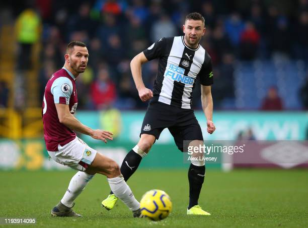 Paul Dummett of Newcastle United battles for possession with Phil Bardsley of Burnley during the Premier League match between Burnley FC and...