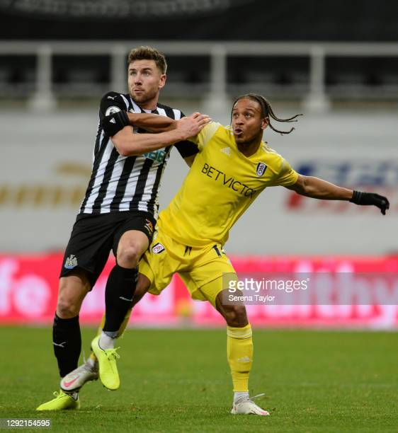 Paul Dummett of Newcastle United FC and Bobby Decordova-Reid of Fulham FC jostle for the ball during the Premier League match between Newcastle...
