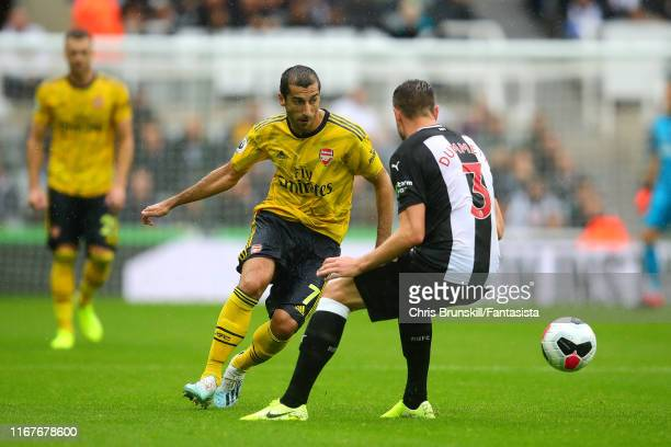 Paul Dummett of Newcastle United in action with Henrikh Mkhitaryan of Arsenal during the Premier League match between Newcastle United and Arsenal FC...