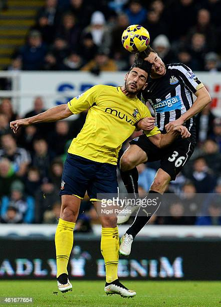 Paul Dummett of Newcastle United jumps for the ball with Graziano Pelle of Southampton during the Barclays Premier League match between Newcastle...