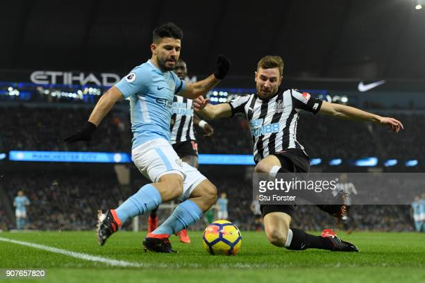 Paul Dummett of Newcastle United tackles Sergio Aguero of Manchester City during the Premier League match between Manchester City and Newcastle...