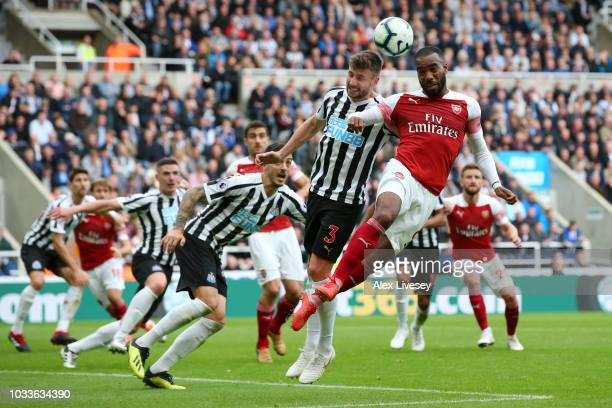 Paul Dummett of Newcastle United wins a header over Alexandre Lacazette of Arsenal during the Premier League match between Newcastle United and...
