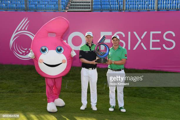 Paul Dunne and Gavin Moynihan of Ireland celebrate victory with the trophy and mascot during day two of the GolfSixes at The Centurion Club on May 6...