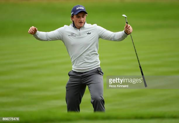 Paul Dunne of Ireland celebrates after chipping in on the 18th hole to win the tournament during day four of the British Masters at Close House Golf...