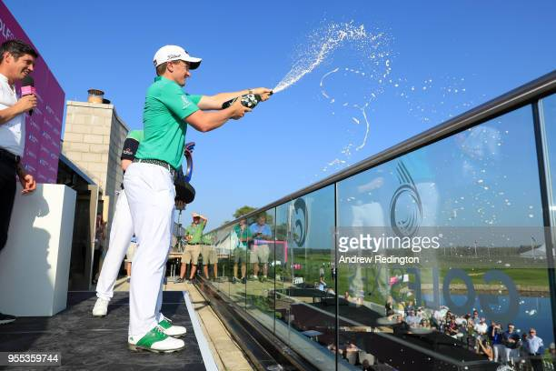 Paul Dunne of Ireland celebrates victory with champagne during day two of the GolfSixes at The Centurion Club on May 6 2018 in St Albans England