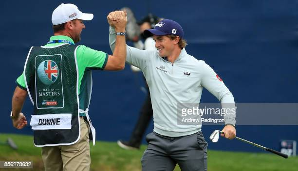 Paul Dunne of Ireland celebrates with his caddie Darren Reynolds after chipping in on the 18th hole to win the tournament during day four of the...