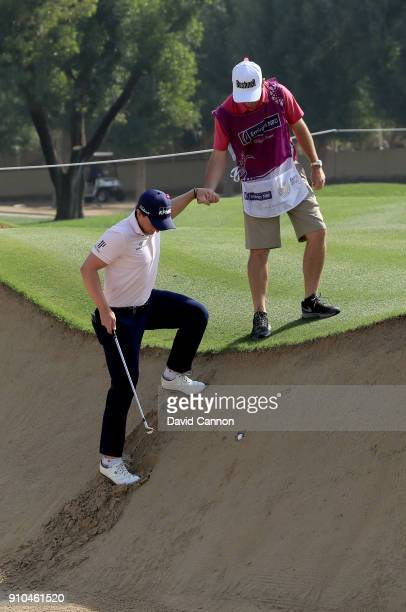 Paul Dunne of Ireland is helped by his caddie after his ball for his third shot had plugged in the face of the greenside bunker on the par 5, 10th...