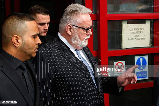 Paul Flowers former chairman of CoOperative Bank Plc right leaves Leeds Magistrates Court in Leeds UK on Wednesday May 7 2014 Flowers the former...