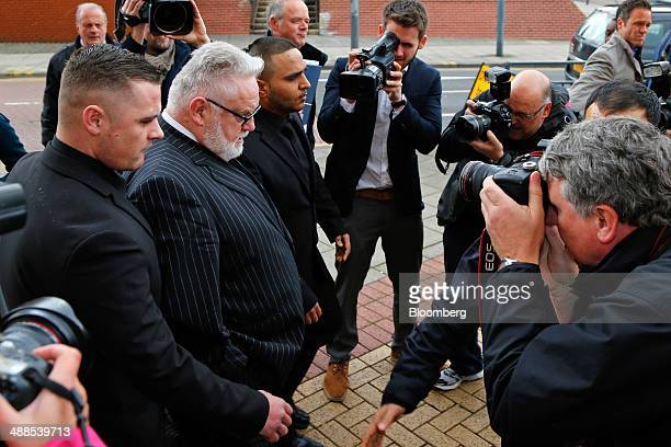 Paul Flowers former chairman of CoOperative Bank Plc second left arrives at Leeds Magistrates Court in Leeds UK on Wednesday May 7 2014 Flowers the...