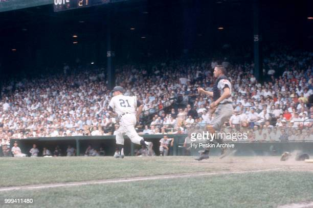 Paul Foytack of the Detroit Tigers runs to first after getting the bunt down as catcher Dick Brown of the Cleveland Indians runs out from behind the...