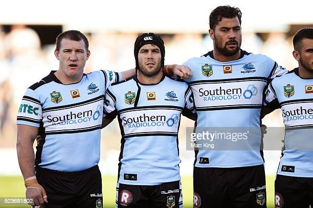 Paul Gallen Michael Ennis and Andrew Fifita of the Sharks line up for the national anthems and Anzac Day commemorations during the round eight NRL...