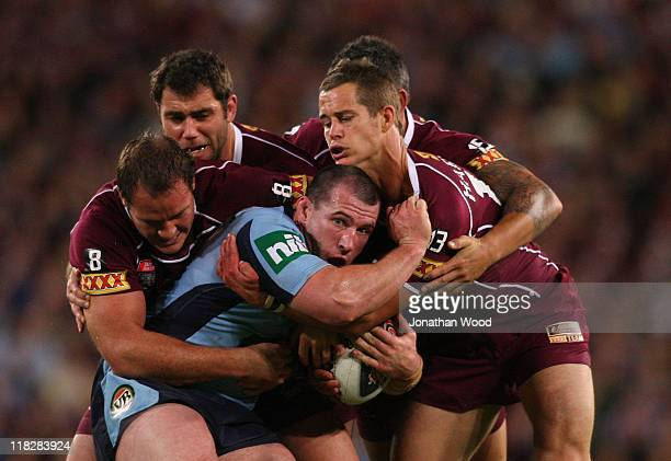 Paul Gallen of the Blues is tackled during game three of the ARL State of Origin series between the Queensland Maroons and the New South Wales Blues...