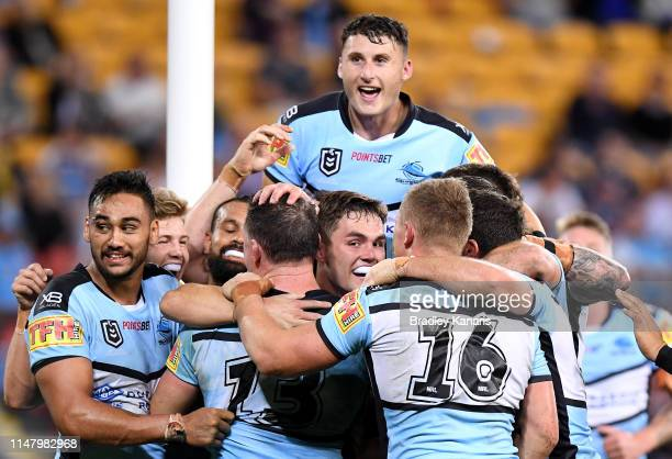 Paul Gallen of the Sharks is congratulated by team mates after scoring a try during the round nine NRL match between the Gold Coast Titans and the...