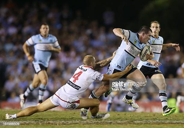 Paul Gallen of the Sharks is tackled by Matt Cooper of the Dragons during the round four NRL match between the Cronulla Sharks and the St George...