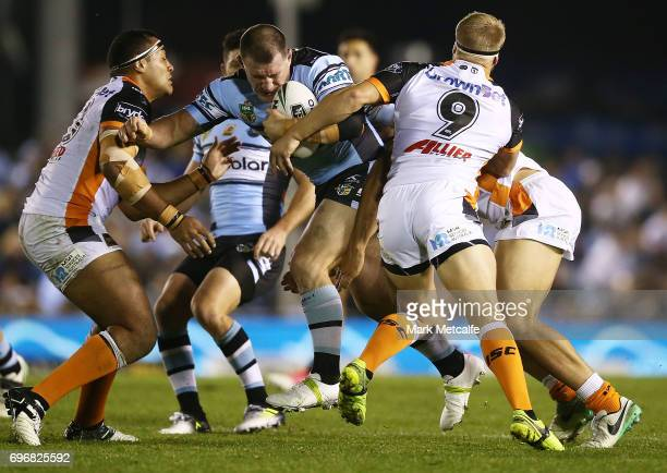 Paul Gallen of the Sharks is tackled during the round 15 NRL match between the Cronulla Sharks and the Wests Tigers at Southern Cross Group Stadium...