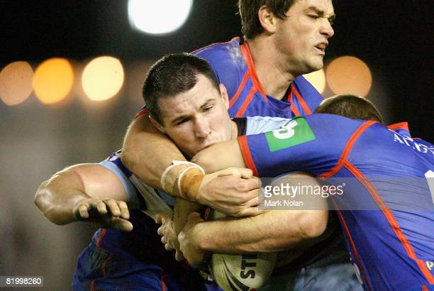 Paul Gallen of the Sharks is tackled during the round 19 NRL match between the Cronulla Sharks and the Newcastle Knights at Toyota Stadium on July...