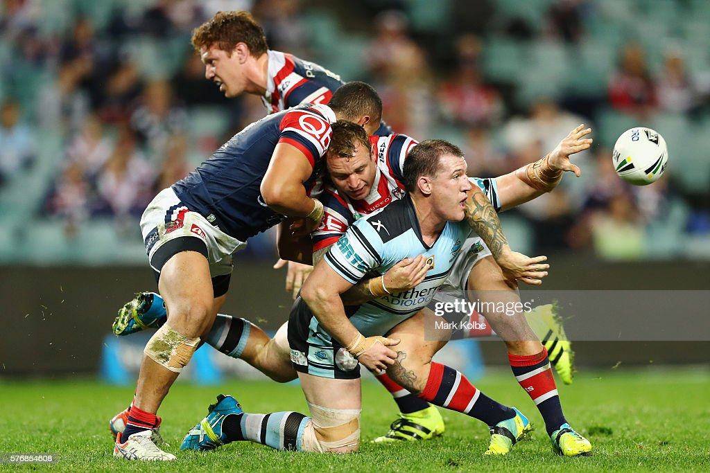 Paul Gallen of the Sharks passes as he is tackled during the round 19 NRL match between the Sydney Roosters and the Cronulla Sharks at Allianz Stadium on July 18, 2016 in Sydney, Australia.