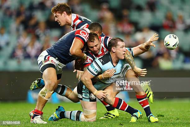 Paul Gallen of the Sharks passes as he is tackled during the round 19 NRL match between the Sydney Roosters and the Cronulla Sharks at Allianz...