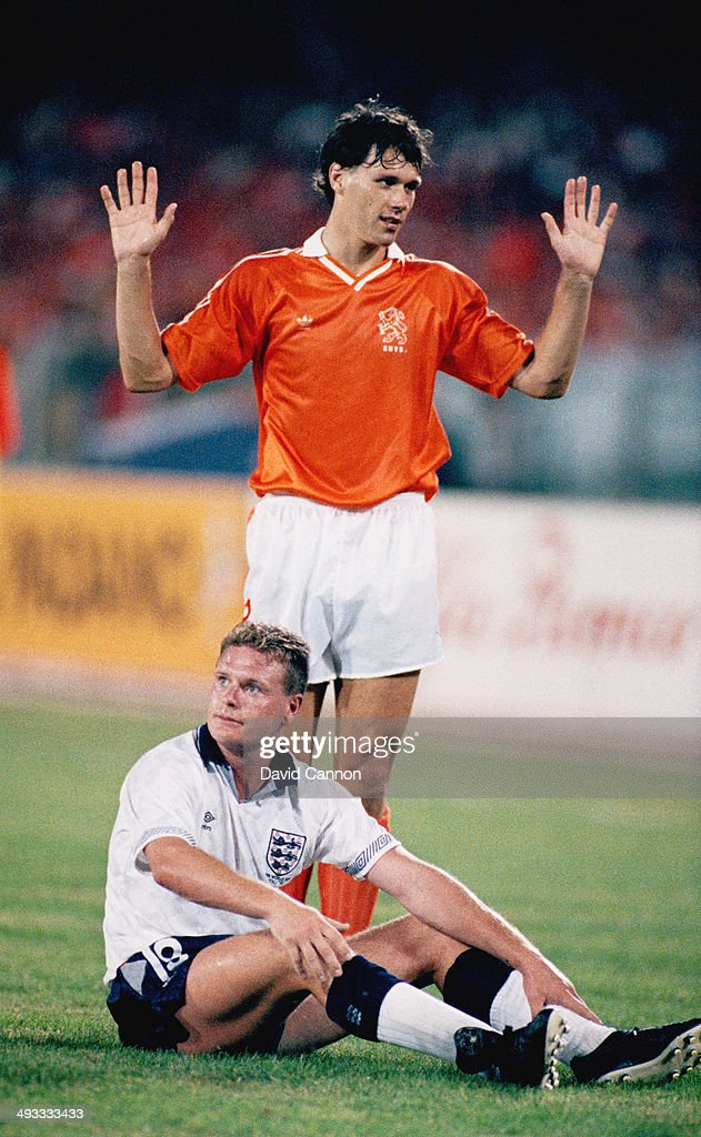 Paul Gascoigne of England (floor) looks on as Marco Van Basten of Holland reacts during the FIFA World Cup Finals 1990 group match between Holland and England at the Sant' Elia Stadium on June 16, 1990 in Cagliari, Italy.