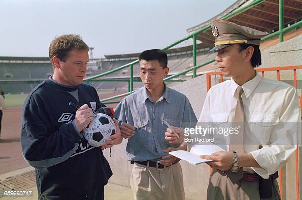 Paul Gascoigne signs a ball for fans during the England football team's tour of Hong Kong and China China May 1996