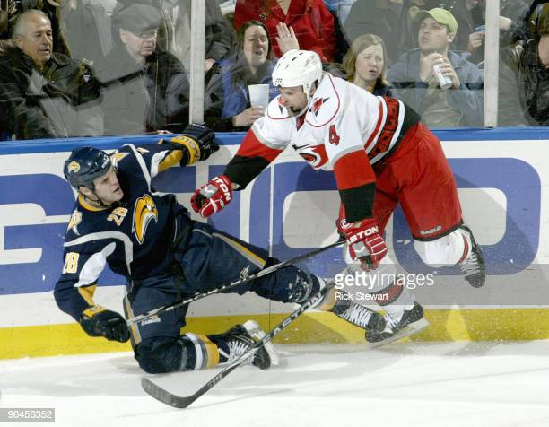 Paul Gaustad of the Buffalo Sabres is checked by Aaron Ward of the Carolina Hurricanes at HSBC Arena on February 5 2010 in Buffalo New York