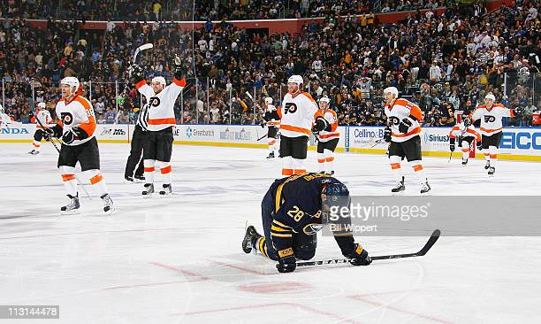 Paul Gaustad of the Buffalo Sabres reacts as the Philadelphia Flyers celebrate the game winning overtime goal scored by Ville Leino in Game Six of...