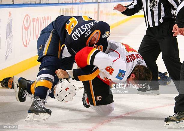Paul Gaustad of the Buffalo Sabres tries to look through the collar of his jersey while fighting with Dion Phaneuf of the Calgary Flames on November...