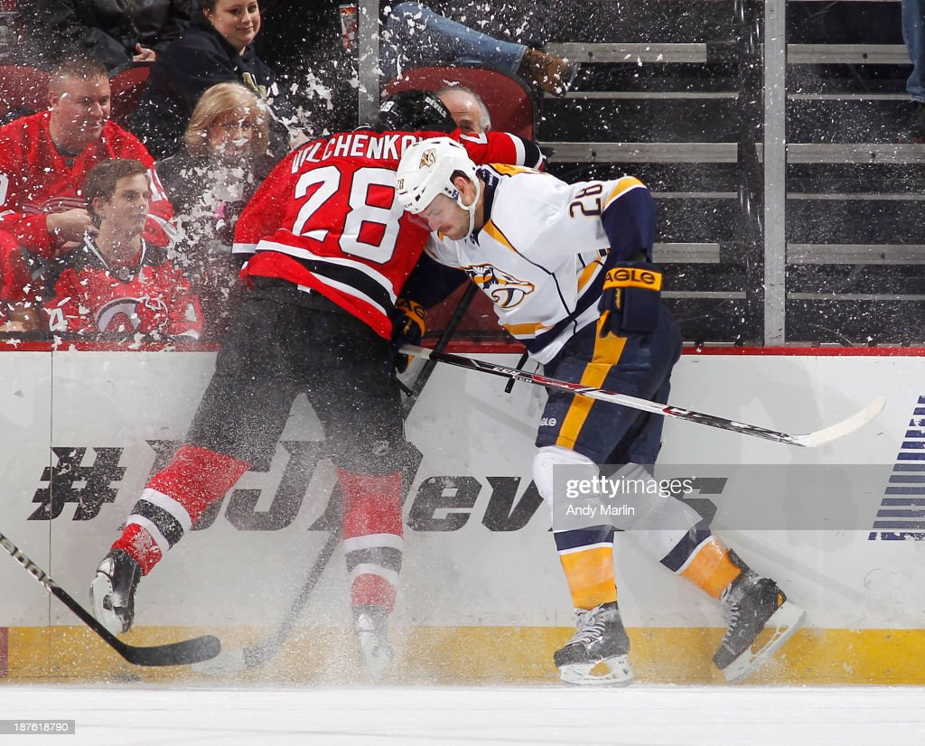 Paul Gaustad #28 of the Nashville Predators and Anton Volchenkov #28 of the New Jersey Devils battle for position along the boards during the game at the Prudential Center on November 10, 2013 in Newark, New Jersey.