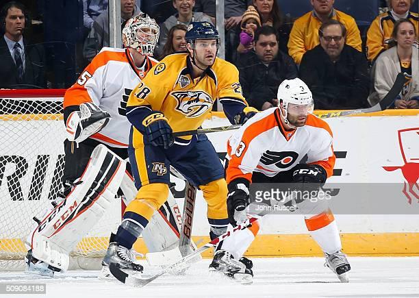 Paul Gaustad of the Nashville Predators battles against Radko Gudas and Steve Mason of the Philadelphia Flyers during an NHL game at Bridgestone...