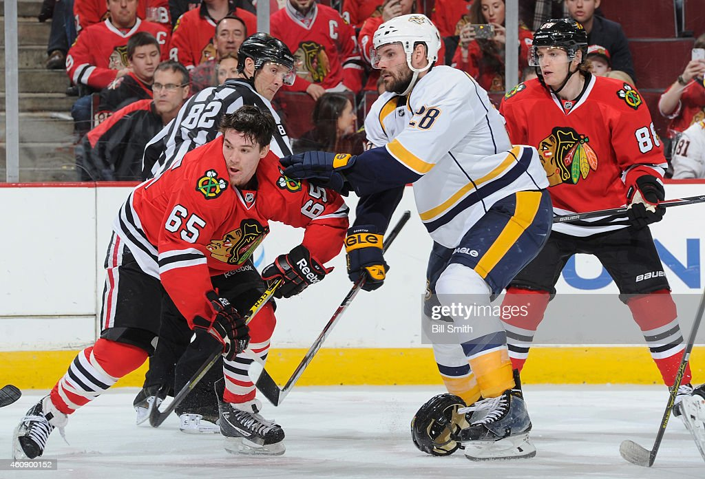Paul Gaustad #28 of the Nashville Predators stands in between Andrew Shaw #65 and Patrick Kane #88 of the Chicago Blackhawks during the NHL game at the United Center on December 29, 2014 in Chicago, Illinois.