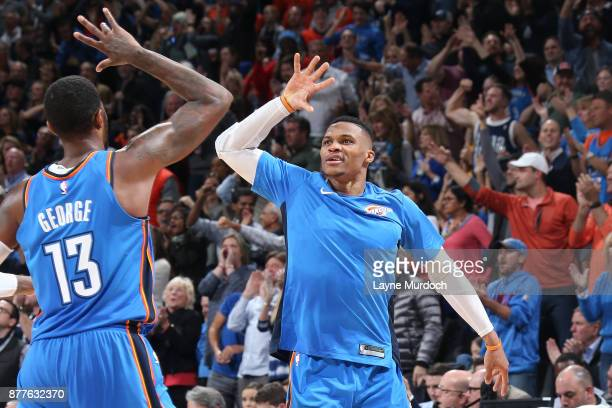 Paul George and Russell Westbrook of the Oklahoma City Thunder high five during the game against the Golden State Warriors on November 22 2017 at...