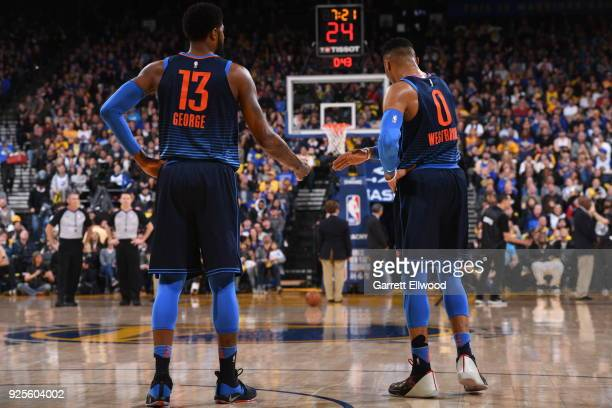 Paul George and Russell Westbrook of the Oklahoma City Thunder high five during the game against the Golden State Warriors on February 24 2018 at...