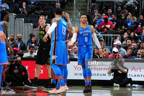 Paul George and Russell Westbrook of the Oklahoma City Thunder react during game against the Atlanta Hawks on March 13 2018 at Philips Arena in...