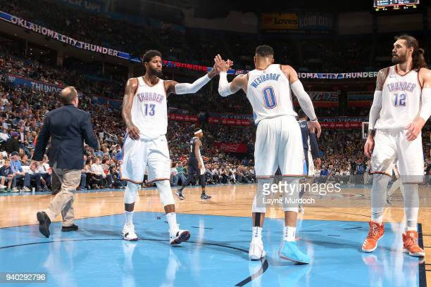 Paul George and Russell Westbrook of the Oklahoma City Thunder react to a play during the game against the Denver Nuggets on March 30 2018 at...