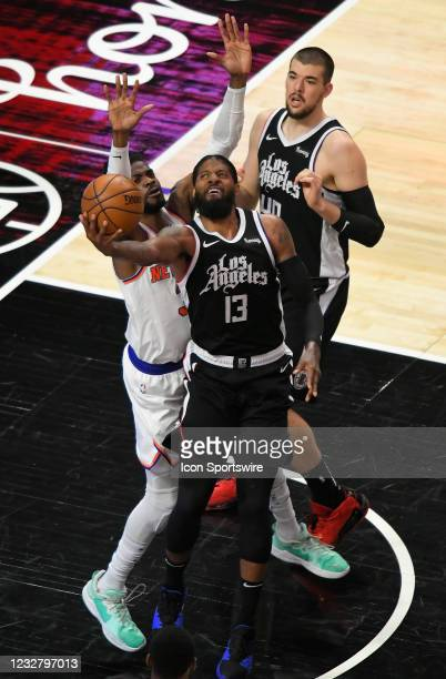Paul George lays the ball up against Nerlens Noel of the New York Knicks as Ivica Zubac of the LA Clippers looks on in the first half during the Los...