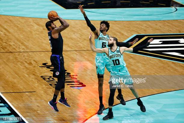 Paul George of the LA Clippers attempts a three point basket against Caleb Martin and Jalen McDaniels of the Charlotte Hornets during the second...