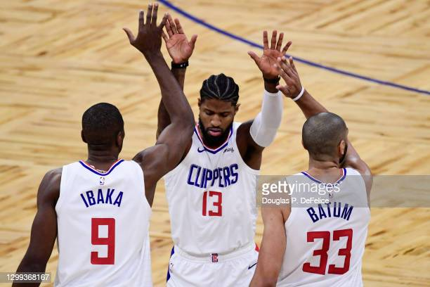 Paul George of the LA Clippers celebrates with teammates Serge Ibaka and Nicolas Batum during the first quarter against the Orlando Magic at Amway...