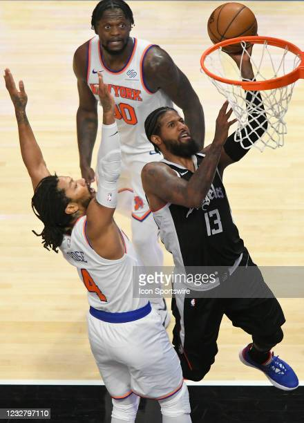 Paul George of the LA Clippers gets past Derrick Rose for a layup while Julius Randle of the New York Knicks looks on in the second half during the...
