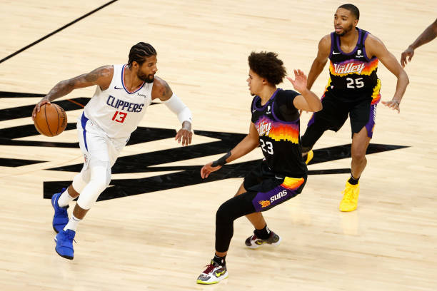 Paul George of the LA Clippers handles the ball against Cameron Johnson of the Phoenix Suns during the second half of game one of the Western...