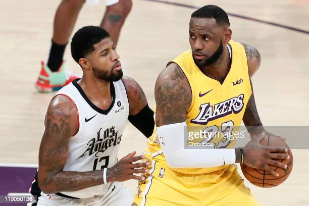 Paul George of the LA Clippers plays defense on LeBron James of the Los Angeles Lakers on December 25 2019 at STAPLES Center in Los Angeles...