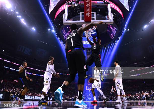 Paul George of the LA Clippers scores on a dunk in front of Reggie Jackson during a 132 103 win over the Denver Nuggets at Staples Center on February...