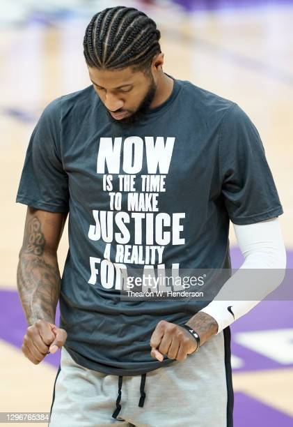 "Paul George of the LA Clippers warming up wears a Nike basketball shooting shirt that displays on the font ""Now Is The Time To Make Justice A Reality..."