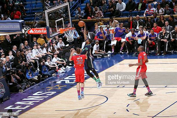 Paul George of the Eastern Conference AllStars dunks against Blake Griffin of the Western Conference AllStars during the 2014 NBA AllStar Game at...