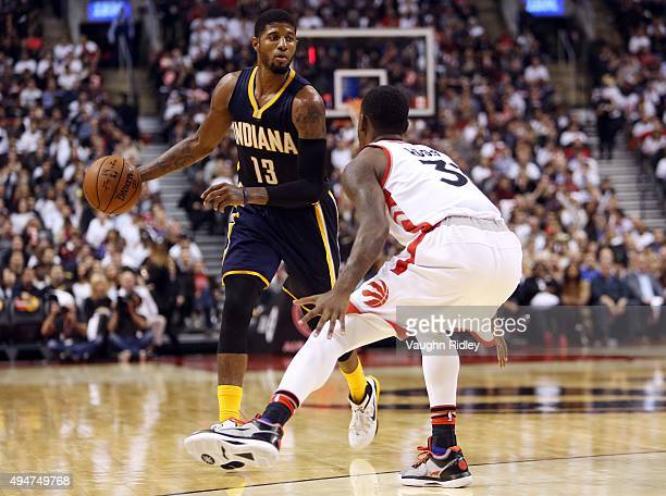 Paul George of the Indiana Pacers dribbles past Terrance Ross of the Toronto Raptors during the NBA season opener at Air Canada Centre on October 28...