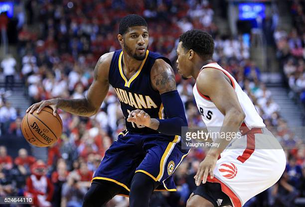 Paul George of the Indiana Pacers dribbles the ball as Kyle Lowry of the Toronto Raptors defends in the first half of Game Five of the Eastern...