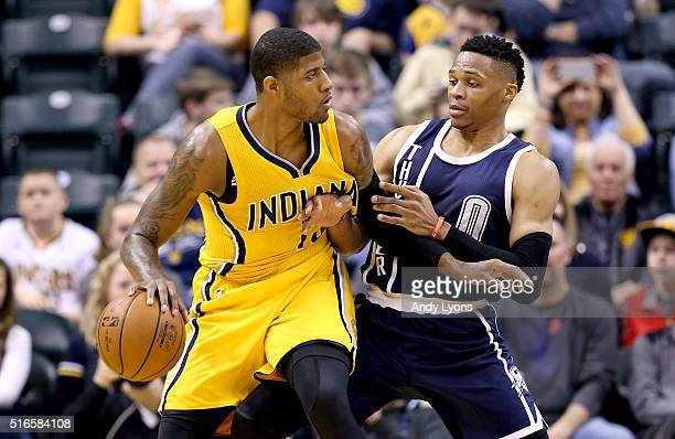 Paul George of the Indiana Pacers dribbles the ball while defended by Russell Westbrook of the Oklahoma City Thunder at Bankers Life Fieldhouse on...