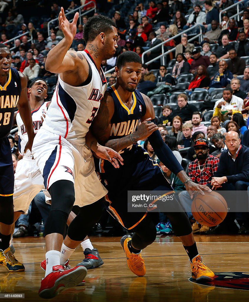 Paul George #24 of the Indiana Pacers drives against Mike Scott #32 of the Atlanta Hawks at Philips Arena on January 8, 2014 in Atlanta, Georgia.