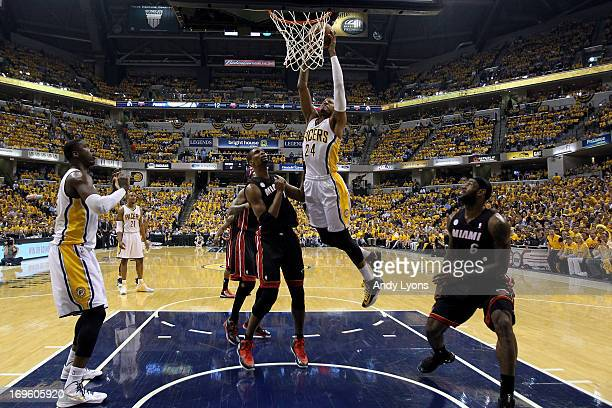 Paul George of the Indiana Pacers drives for a dunk attempt against Chris Bosh and LeBron James of the Miami Heat during Game Four of the Eastern...
